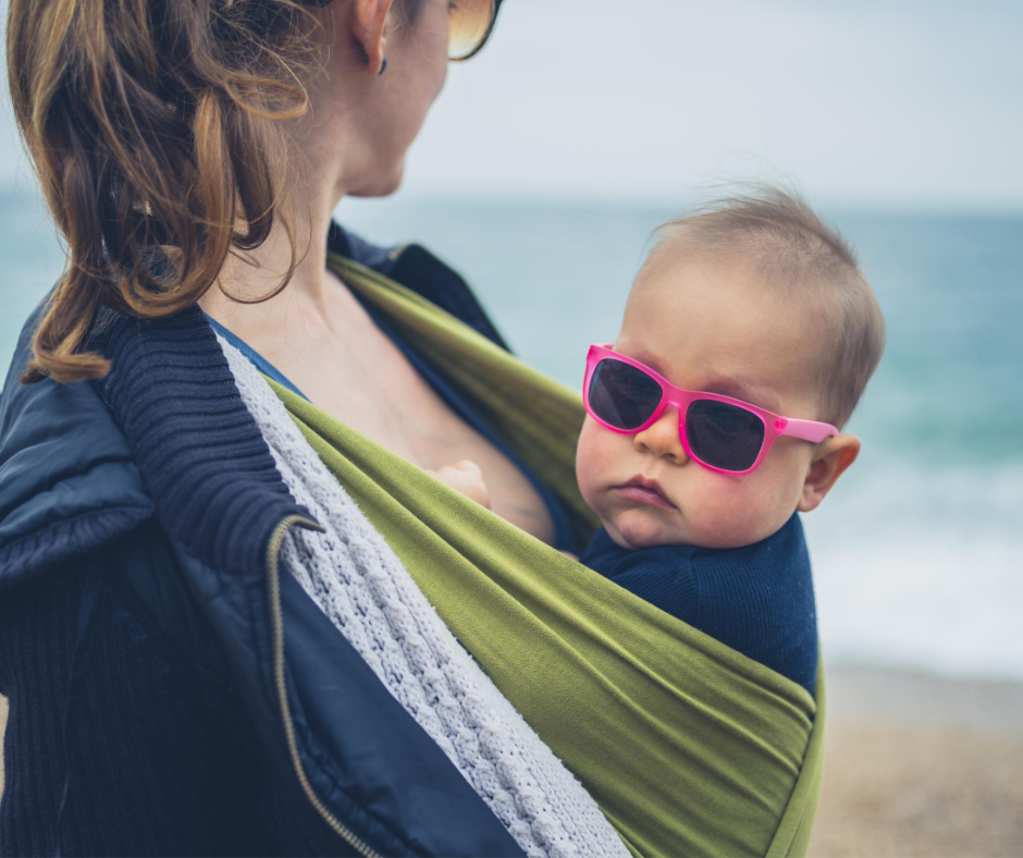 Baby with sunglasses in sling with mom