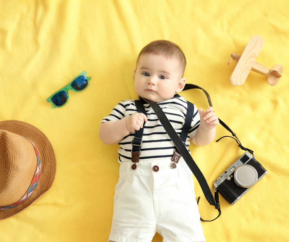 baby on yellow blanket with camera sunglasses hat